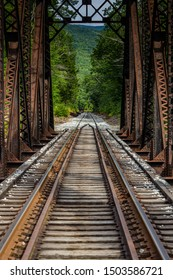 Abandoned railroad tracks under an old, iron trestle running to nowhere in New Hampshire