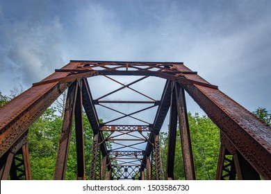 Abandoned railroad trestle against an overcast sky in New Hampshire