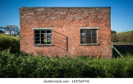 An abandoned red brick building on an industrial site.