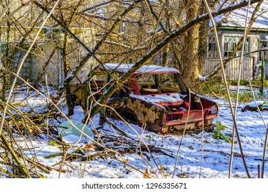 Abandoned red car covered in snow in Chernobyl Exclusion Zone, Ukraine