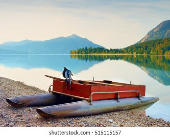 Abandoned red gray fishing boat on bank of Alpine  lake. Autumnal morning at  lake  in gentle sunlight. Picturesque scene. Mountains in water mirror.