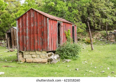 Abandoned red shack with brown shack in background and stone foundation in disrepair