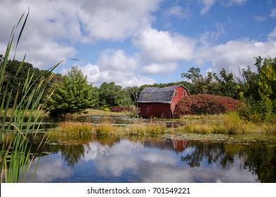 An abandoned red sinking barn sinks into a lake near Zimmerman, Minnesota