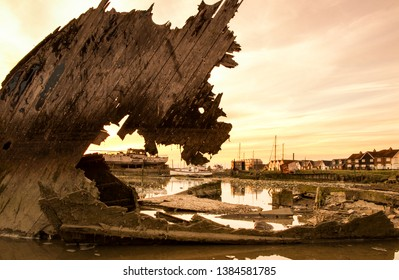 The abandoned remnants of a wood boat take on a mysterious silhouette at sunset as it naturally decays. Pareidolia where the imagination suggests a mythical dragon on the River Arun, Littlehampton.