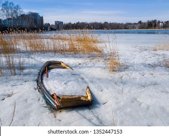Abandoned rowing boat full of ice and snow in the middle of reeds and ice by the Baltic Sea in Espoo, Finland