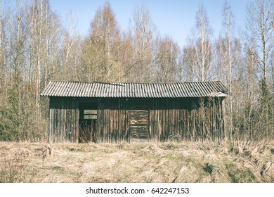 Abandoned ruins of old wooden building in latvia countryside - vintage green look