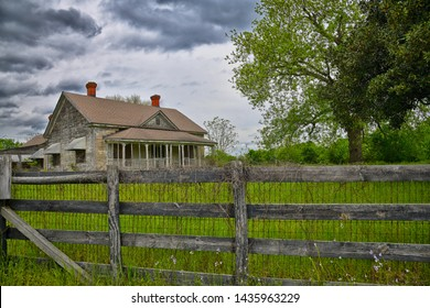 Abandoned Rural Farmhouse with Wooden Fence and Large Tree in Yard