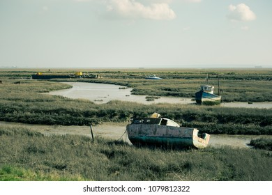 abandoned rusted boats on low tidal grounds in Essex, UK