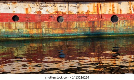 Abandoned and rusting boat with three portholes and its reflection in the water. Detail. Painting - like photo.