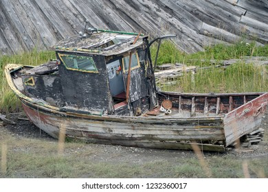 An abandoned rusty boat sits in a marshy grass field along the Homer Spit, along the Kachemak Bay in Homer Alaska