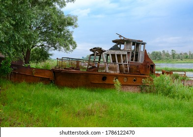 Abandoned rusty ship on river bank in exclusion zone of Chernobyl nuclear power plant near village Krasnoselie, Khoiniki district, Belarus