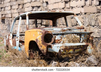 Abandoned and rusty skeleton of a Soviet Russian car growing hay inside by the side of the building exterior in Ararat province on 4 April 2017.