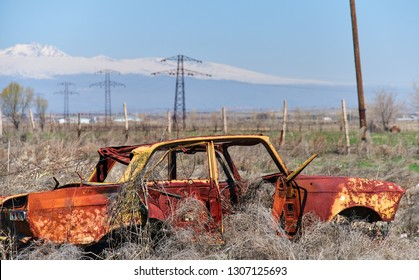 Abandoned and rusty wreckage of an yellow vintage Soviet Russian car in the middle of dry hay with scenic ice top mountains and clear blue sky on the background in rural Southern Armenia.