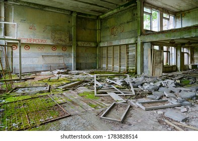 """Abandoned school gym in large resettled village of Pogonnoe in exclusion zone of Chernobyl nuclear power plant, Khoiniki district, Gomel region, Belarus. Text on wall: """"From pioneer starts"""""""