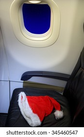 Abandoned seat flying aircraft with Santa cap. Evening at the plane with an empty seat and forgotten Santa Claus hat.