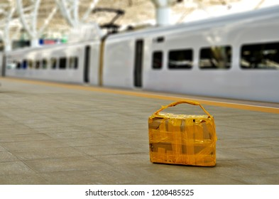 Abandoned self made carton suitcase laying on railway station quay platform floor in China. Looking suspect, nobody around, fast train in background.