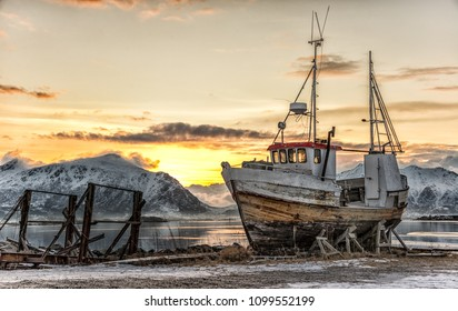 Abandoned ship in Lofoten, Norway with sun rising behind