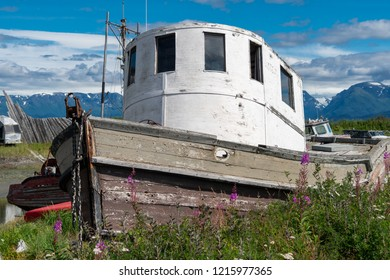 Abandoned shipwreck sits in a junkyard along the Homer Spit in Alaska on a sunny day