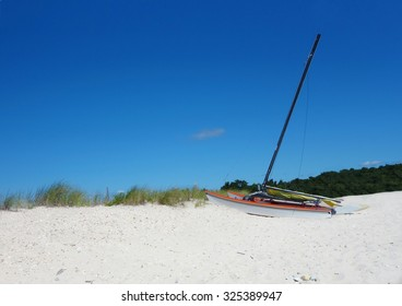 Abandoned solitary sailing boat lying on the sand dunes