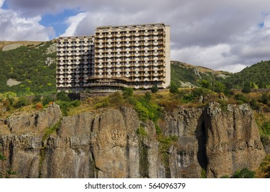 Abandoned soviet hotel on the cliff of Arpa river canyon on spa resort city Jermuk, Armenia
