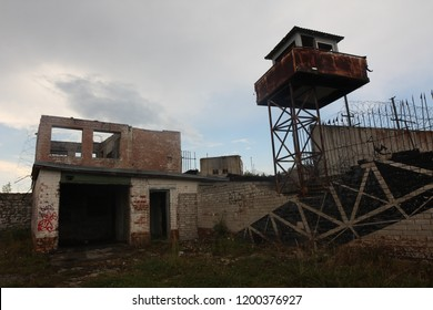 Abandoned soviet Russian military prison complex in Estonia. Watchtowers and rusty razor wire barbed fences border boundary walls. Dramatic interesting frightening unwelcoming.