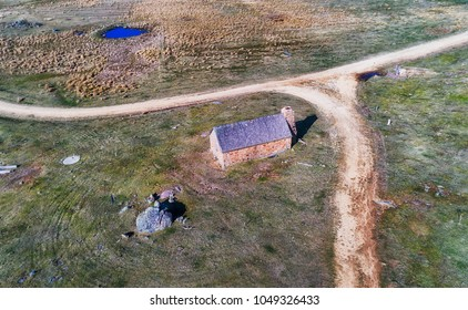 Abandoned stone farm house hut near Crackenback in Thredbo valley of Snowy mountains, Australia. Aerial view over the house and nearby unsealed road with grassy plain.