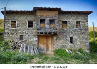 abandoned stone house with firewood next to the front door filled with straw
