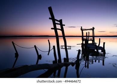 Abandoned Sunken Pier on a Calm Lake at Sunrise