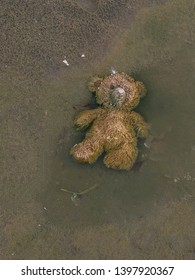 An abandoned teddy bear on the beach side and it is creepy