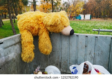 Abandoned teddy bear in the trash can. The symbol of leaving childhood, growing up