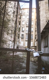 Abandoned tenant house, with a gate closed with a padlock in the foreground, in Warsaw, Poland