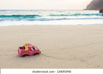 Abandoned toy truck on the beach at sunrise