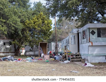 An abandoned trailer home with mountains of trash littering the yard