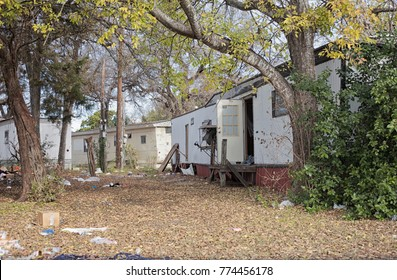 An abandoned trailer home with open door & trash littering the yard