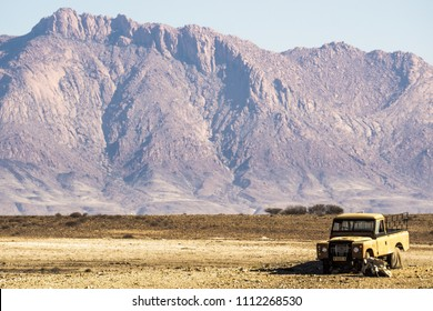 Abandoned truck with impressive mountains in the background. Brandberg, Namibia, Africa.