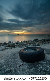Abandoned and Unlabelled tyre on the muddy sunset beach impliedly show the pollution