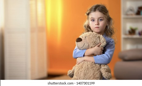 Abandoned upset curly girl holding favorite teddy bear feeling sad in orphanage