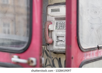 Abandoned and vandalized payphone with ajar phone booth door