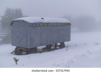 Abandoned wagon house at foggy winter day