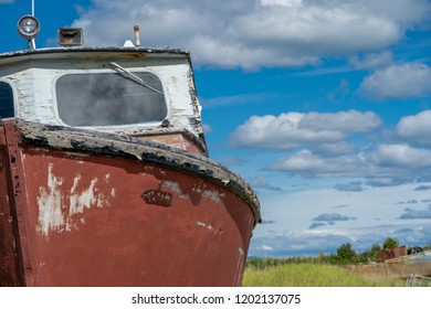 An abandoned and weathered red rusty boat sits in a marshy grass field along the Homer Spit, along the Kachemak Bay in Homer Alaska