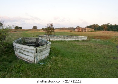Abandoned wooden boats on shore. Sunrise and green meadows. Shed in the background.