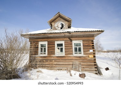 Abandoned wooden house in the Russian village. Round-lucarnes window on the facade. Russia, Arkhangelsk Oblast