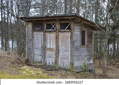 Abandoned wooden outdoor toilet with three doors in a forest.
