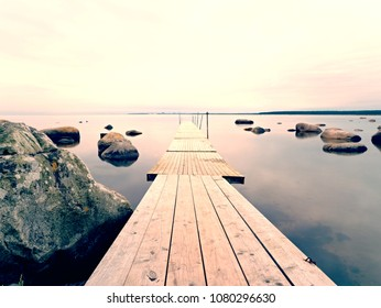 Abandoned wooden wharf mole in sea within sunrise. Gentle blue pink color of sky blurry waves on water level.