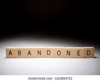 Abandoned word in blocks on white table with elegant lightning. Abandoned concept