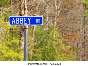 An Abbey road sign against the woods honoring the famed Beatles recording studio in London using selective focus and a shallow depth of field with room for your text.