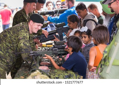 ABBOTSFORD, BC, CANADA - AUG 11, 2019: A Canadian Armed Forces soldier showing children an automatic rifle at the Abbotsford International Airshow.