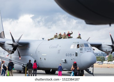 ABBOTSFORD, BC, CANADA - AUG 11, 2019: RCAF military personnel sitting atop a C-130 Hercules at the Abbotsford International Airshow.