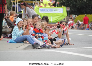 ABBOTSFORD, BC/CANADA  ?? JULY 1 2016: Patriotic children watch a Canada Day parade in Abbotsford, British Columbia, Canada on July 1, 2016.