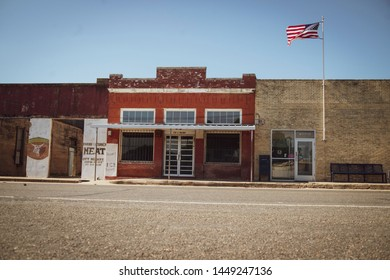 Abbott, Texas - July 11 2019: rural downtown buildings abandoned US flag